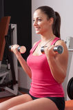 Beautiful smiling woman exercising with dumbbells Royalty Free Stock Images