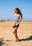 Beautiful smiling woman with fashion bag posing on the beach bac Royalty Free Stock Photos