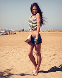 Beautiful smiling woman with fashion bag posing on the beach bac Stock Image