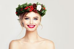 Beautiful Smiling Woman Fashion Model. Happy Girl with Christmas or New Year Wreath with Green Xmas Tree Twig, Red Decor and Berry. Cute Female Face Closeup Stock Photography