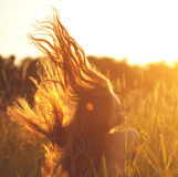 Beautiful smiling woman in a field at sunset. Trendy young girl Stock Photography