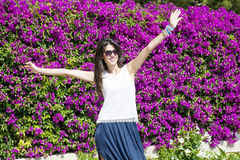 Beautiful smiling woman  in front of bougainvilleas flowers Stock Photo