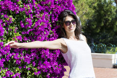 Beautiful smiling woman  in front of bougainvilleas flowers Royalty Free Stock Images