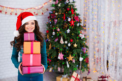 Beautiful smiling woman with gifts at the Christmas tree. Royalty Free Stock Photo