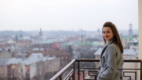 Beautiful smiling woman in grey coat staying on the balcony and posing on camera. stock footage