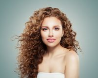 Beautiful smiling woman with healthy curly hair on gray background. Redhead girl royalty free stock image
