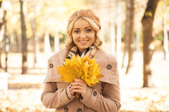 Beautiful smiling woman holding a bouquet of golden foliage Royalty Free Stock Image