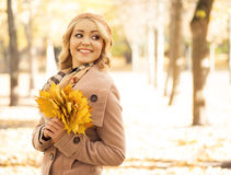 Beautiful smiling woman holding a bouquet of golden foliage Stock Images