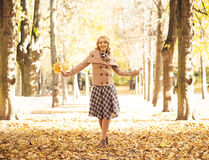Beautiful smiling woman holding a bouquet of golden foliage Royalty Free Stock Photo