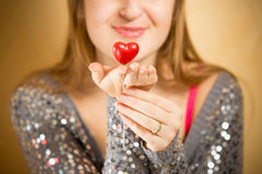 Beautiful smiling woman holding decorative red heart on hand Stock Photography