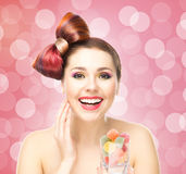 Beautiful smiling woman holding a glass with candies Royalty Free Stock Images