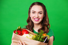 Beautiful smiling woman holding a grocery bag full of fresh and healthy food. on green background Royalty Free Stock Photography