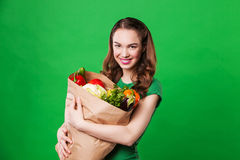 Beautiful smiling woman holding a grocery bag full Royalty Free Stock Photos