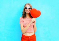 Beautiful smiling woman holding in hand red air balloon heart shape over blue Stock Image
