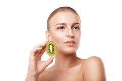 Beautiful smiling woman holding kiwi. Beauty shot Stock Image