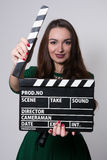 Beautiful smiling woman holding a movie clapper. Stock Images