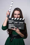 Beautiful smiling woman holding a movie clapper. Royalty Free Stock Photos