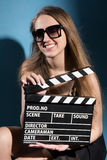 Beautiful smiling woman holding a movie clapper Stock Images