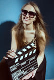 Beautiful smiling woman holding a movie clapper Royalty Free Stock Image