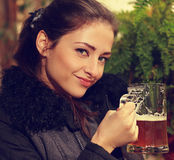 Beautiful smiling woman holding mug of lager beer. Closeup portrait Stock Image