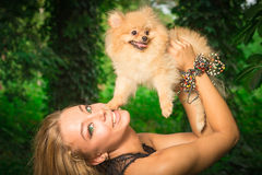 Beautiful smiling woman holding a small dog. On nature Royalty Free Stock Photography