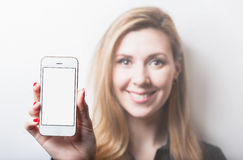 Beautiful smiling woman holding smartphone in hand. Blurred background. Place for text Stock Photography