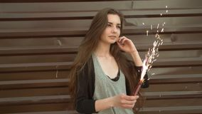 Beautiful smiling woman holding a sparkler on a New Year`s Eve. Slow-motion footage. Warm retro color stock video footage