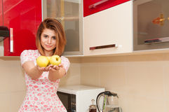 Beautiful smiling woman holding three yellow apples in her hands standing in modern kitchen Royalty Free Stock Images