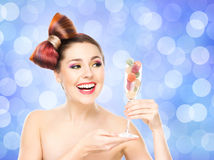Beautiful smiling woman holding a wineglass with candies Stock Photos