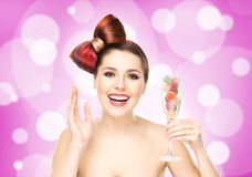 Beautiful smiling woman holding a wineglass with candies Royalty Free Stock Photos