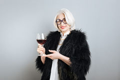 Beautiful smiling woman holding wineglass. Pleasant time. Senior elegant pretty woman smiling and holding wineglass while standing against isolated gray Royalty Free Stock Images