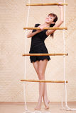Beautiful smiling woman holds on bamboo rope ladder Stock Photo