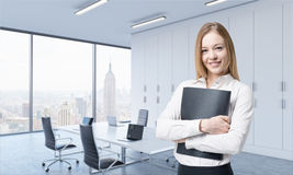 A beautiful smiling woman holds a black document folder in the modern panoramic office. Stock Image