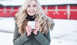 Beautiful smiling woman holds a cup of hot cocoa. royalty free stock photography