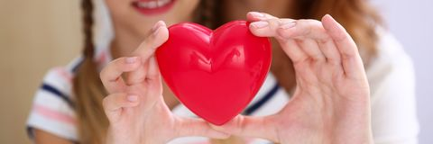 Beautiful smiling woman and kid hold red toy heart Stock Photo
