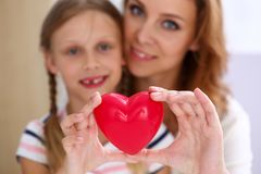Beautiful smiling woman and kid hold red toy heart royalty free stock image