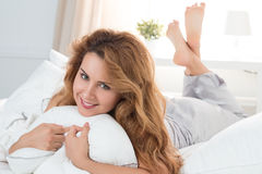 Beautiful smiling woman laying in her bed in the morning Stock Images
