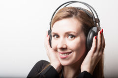 Beautiful smiling woman listening music in headphones Royalty Free Stock Image