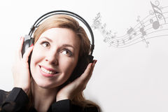 Beautiful smiling woman listening music in headphones Stock Photo