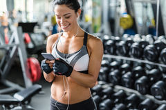 Beautiful Smiling Woman Listening to Music in Gym Royalty Free Stock Image
