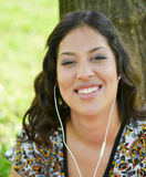 Beautiful smiling woman listening to music outdoors Royalty Free Stock Photos