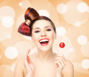 Beautiful smiling woman with a lollipop on bubbly background.  royalty free stock photography