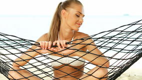 Beautiful smiling woman with long blonde hair sitting cross legged in a hammock stock footage