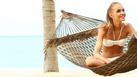 Beautiful smiling woman with long blonde hair sitting cross legged in a hammock stock video