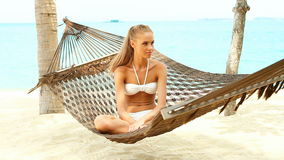 Beautiful smiling woman with long blonde hair sitting cross legged in a hammock stock video footage