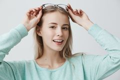 Beautiful smiling woman with long blonde hair and stylish eyewear, has european appearance, looks delightfully, happy to. Beautiful smiling woman with long Royalty Free Stock Image
