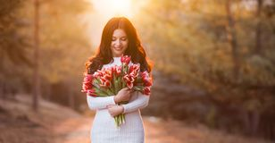 Beautiful smiling woman with spring flowers on sunset background royalty free stock photos