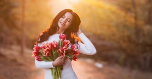 Beautiful smiling woman with spring flowers on sunset background royalty free stock image