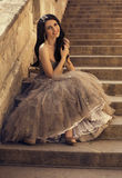 Beautiful smiling woman in luxurious dress sitting on stairs Stock Photography