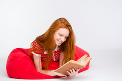 Beautiful smiling woman lying on bean bag and reading  book Stock Images